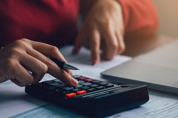 Close up businesswoman using calculator for doing math finance on wooden desk in the office