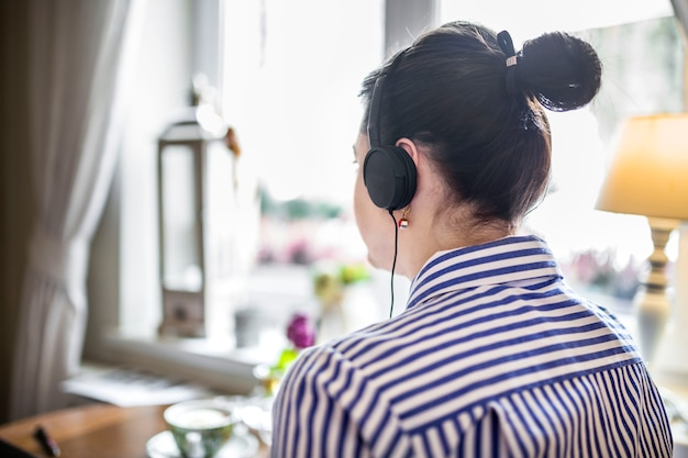 Close-up of a businesswoman using headphone