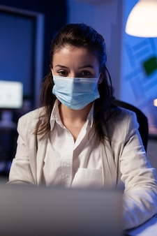 Primo piano di una donna d'affari con maschera facciale che controlla le e-mail a tarda notte nel nuovo normale ufficio aziendale prima della scadenza