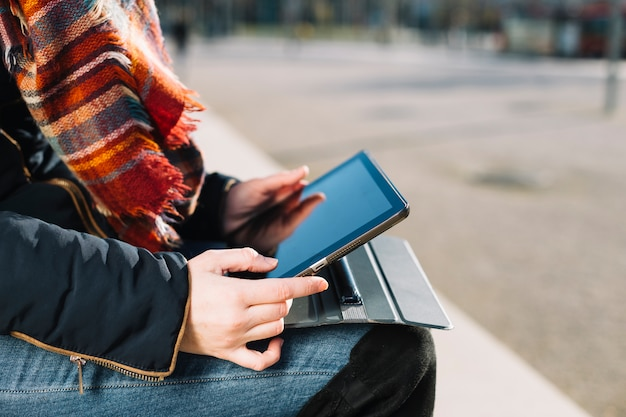 Close up of businesswoman working outdoors with tablet