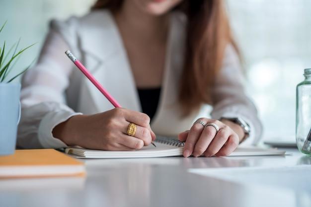 Закройте вверх. предприниматель, писать на пустой записной книжке на столе в офисе.