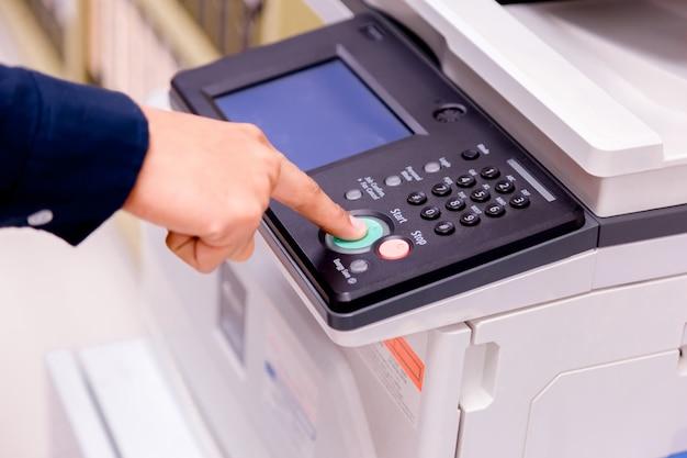クローズアップ商務人プリンターのパネル上の手を押すボタン、プリンタースキャナーレーザーオフィスコピー機用品スタートコンセプト。