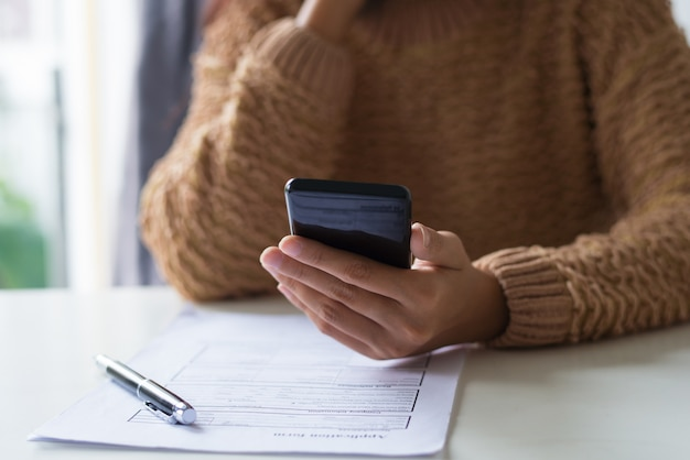 Close-up of busy lady filling document and checking sms on phone