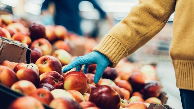 Закройте вверх. покупатель собирает яблоки в магазине