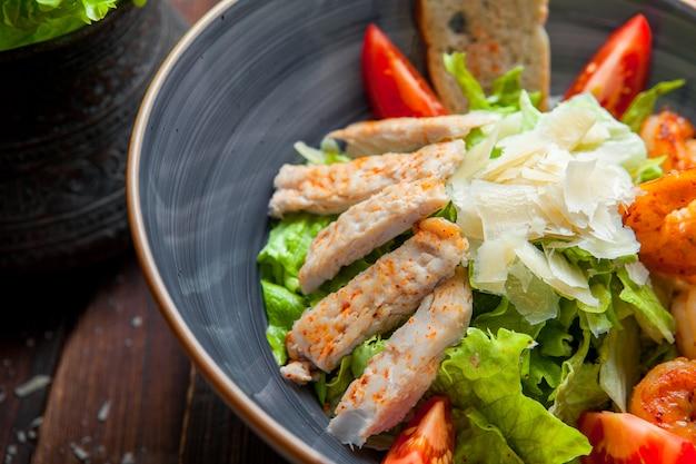 Close up insalata di cesare con petto di pollo e gamberi alla griglia, gamberi, pomodoro, insalata fresca in un piatto su un tavolo di legno scuro