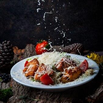 Салат цезарь крупным планом с курицей, помидорами, листьями салата, маслинами, крекерами, сыром пармезан в белой тарелке на темной коре дерева