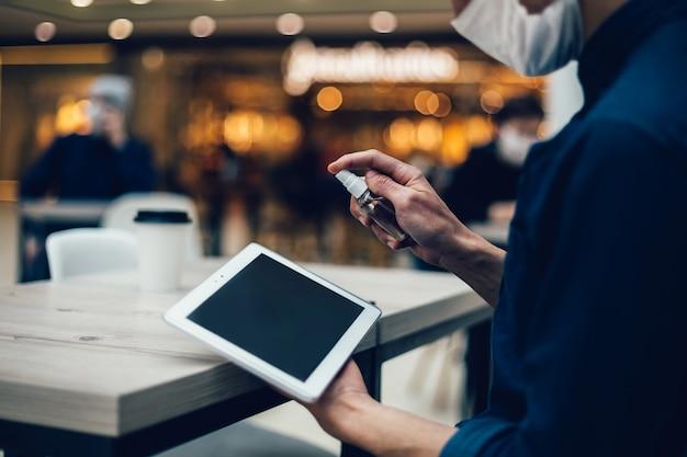 확대 . 디지털 태블릿에 방부제를 뿌리는 카페 방문자. 복사 공간 사진