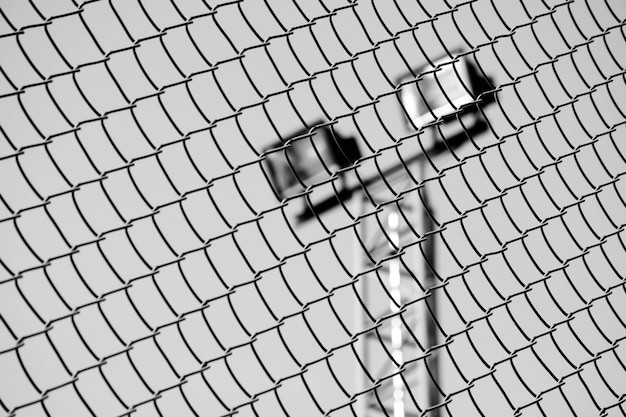 Close up cage metal wire front stadium light - monochrome