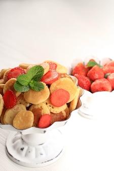 白い背景の上のイチゴ、レモン、ミントの葉と小さなパンケーキシリアルでケーキスタンドを閉じます。トレンディな料理。ミニシリアルパンケーキ。縦向き