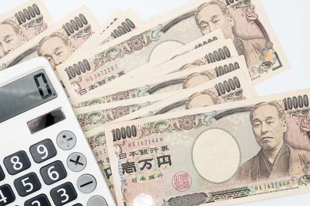 Close up calculator on japanese currency yen money banknote.   japan  economy.