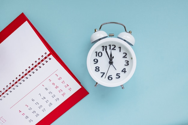 Close up of calendar and alarm clock on the blue background, planning for business meeting or travel planning concept