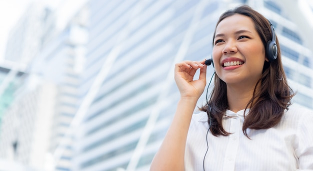 Close up call center employee young asian woman wear headset device and smiling over city building company outdoor