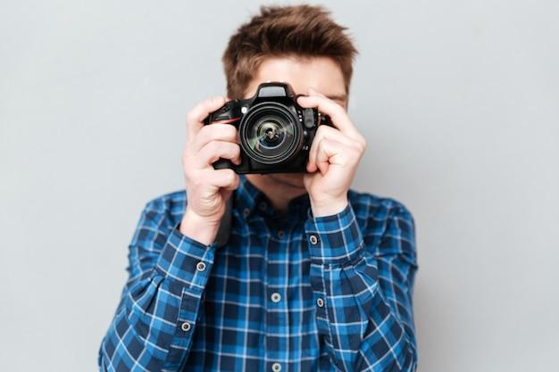 Chiuda in su della macchina fotografica in mani dell'uomo isolate