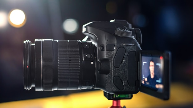 Chiuda in su della fotocamera con l'uomo che parla e si registra in un vlog. lavorare da casa. giovane creatore di contenuti