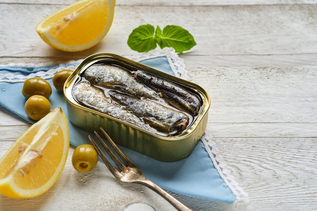 Close-up of can of sardines in oil, with some basil and olive leaves on blue napkin and copy space