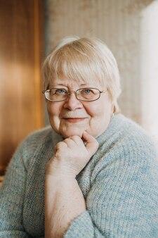 自宅でシニアプラスサイズの金髪の女性の率直な、本物の肖像画をクローズアップ。眼鏡と成熟した女性の肖像画。