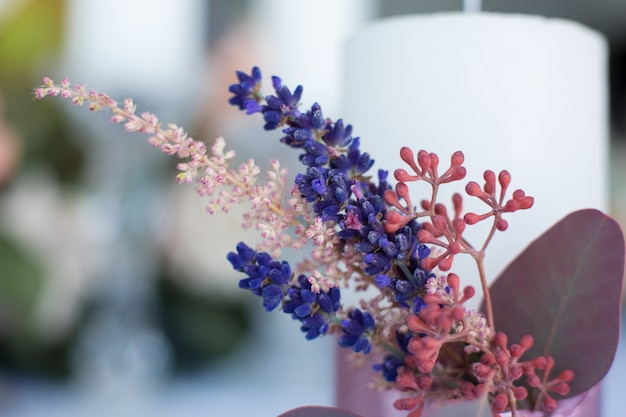 Close up candle decorated with fresh eucalyptus, astilbe and lavender branches bound with pink tape.
