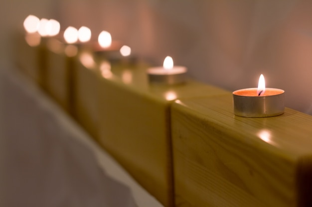 Close-up candles are standing on wooden blocks for yoga, atmosphere for meditation