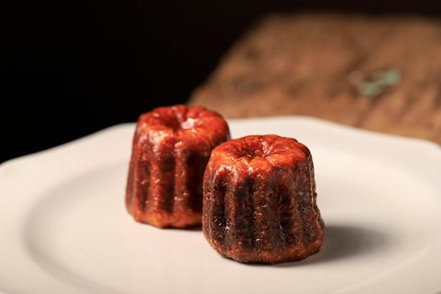 Закройте вверх по пирогу canele bordeaux, французскому сладкому десерту. скопируйте место для текста, квадратного изображения