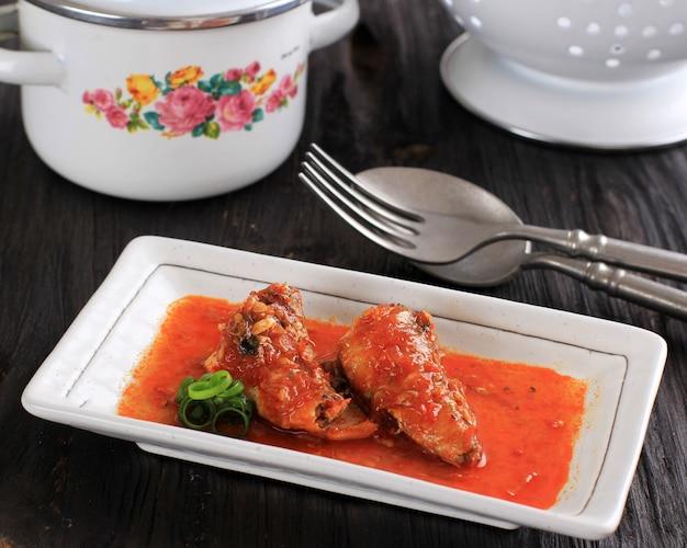 Закройте вверх консервированной сардины с томатным острым соусом, подаваемой на белой тарелке, черном деревянном столе.