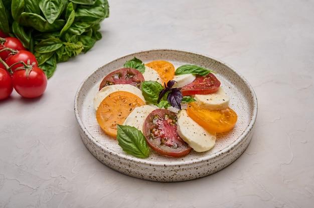 カプレーゼを赤と黄色のトマト、新鮮なバジルとモッツァレラチーズの白いプレートコピーでクローズアップ