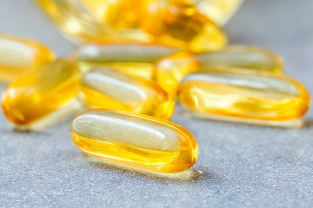Close up capsules fish oil in glass bottle .