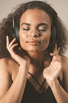 閉じる。目を閉じてヘッドフォンを着用し、灰色の背景で隔離され、感情的に動き、楽しんで音楽を聴いている若いアフリカ系アメリカ人の女の子を音楽でキャプチャします。