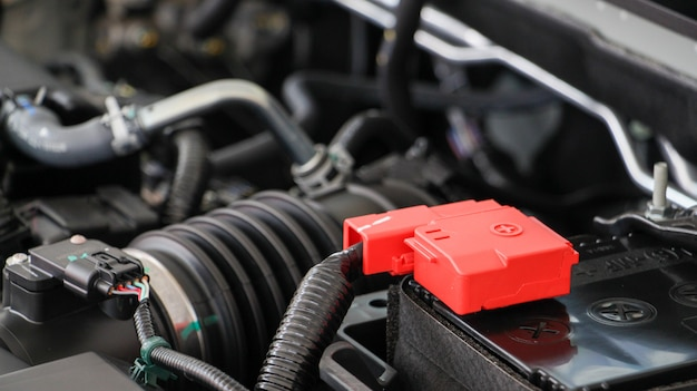 Close up car battery with car engine.