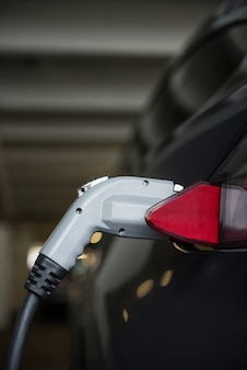Close-up of car being charged with electric car charger