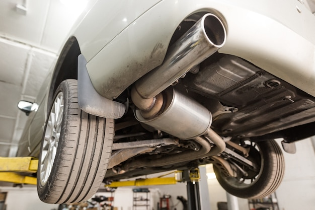 Close up of car exhaust system pipe at the garage, automotive car service