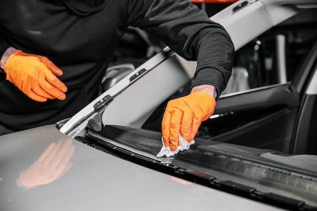 닫기, 자동차 글레이징, 앞 유리 수리 및 수리. 차고 서비스에서 자동차의 앞 유리 교체 프로세스. 대시 보드 청소.
