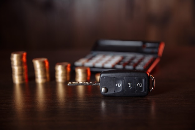 Close-up of car key in front of coins stacked and calculator on wooden table. saving money concept.