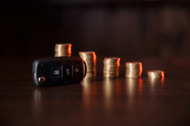 Close-up of car key in front of coins stacked on wooden table. saving money concept.