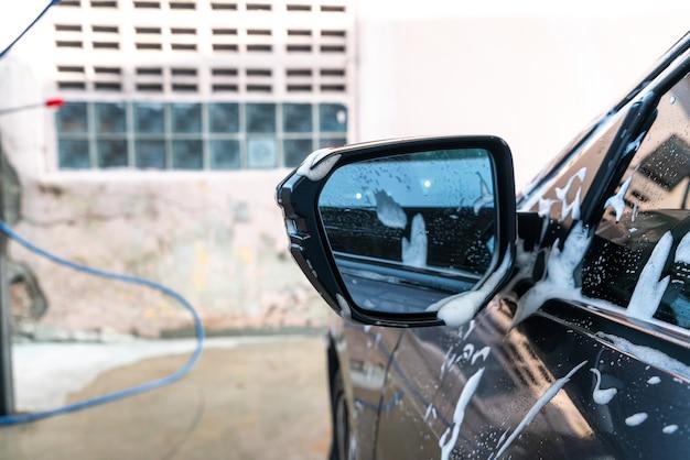 Close-up car side mirror with car washing foam