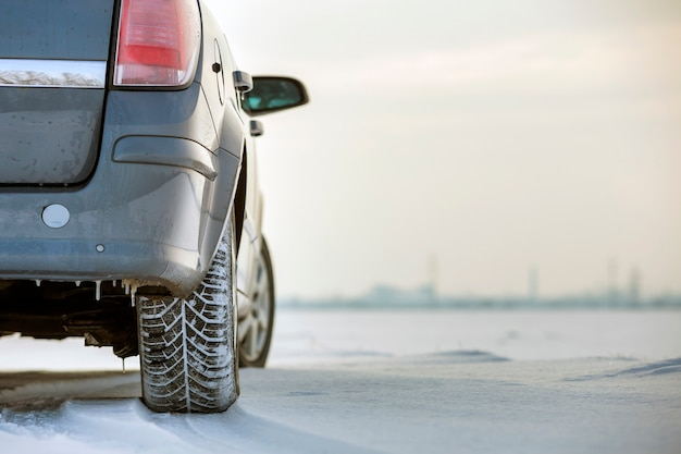 Close up of a car tire parked on snowy road on winter day. transportation and safety concept.