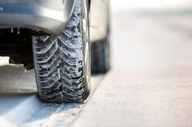 Close-up of car wheel in winter tire on snowy road