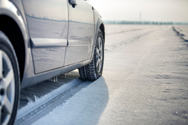 Close-up of car wheels rubber tire in deep snow. transportation and safety concept.