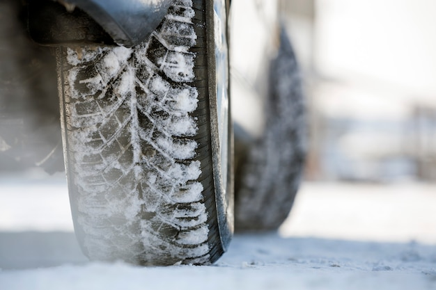 Close-up of car wheels rubber tire in deep snow. transportation and safety .