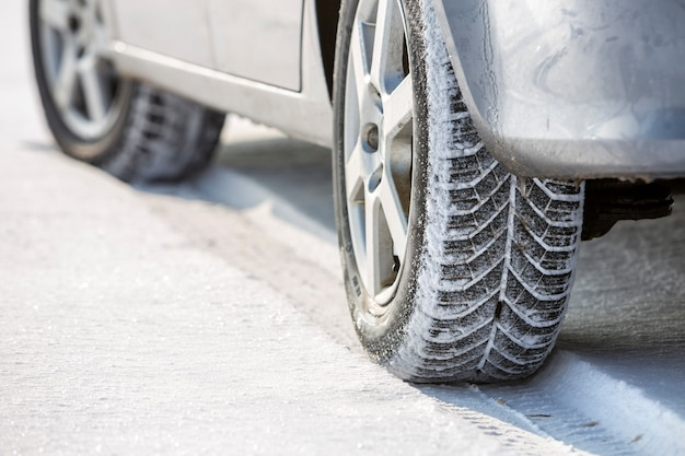 Close-up of car wheels rubber tire in deep snow.