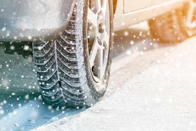Close-up of car wheels rubber tires in deep winter snow. transportation and safety concept.