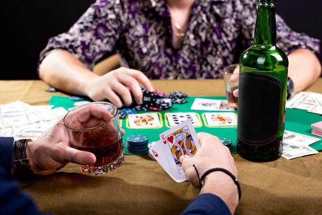 Close up on cards in man's hands on poker table