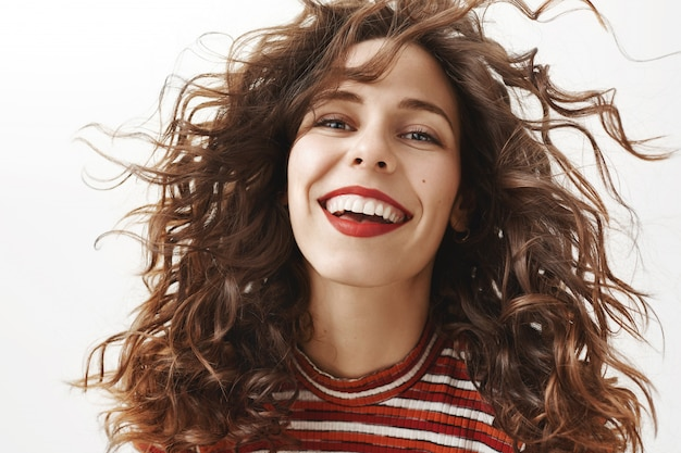 Close-up of carefree attractive woman with curly hair smiling