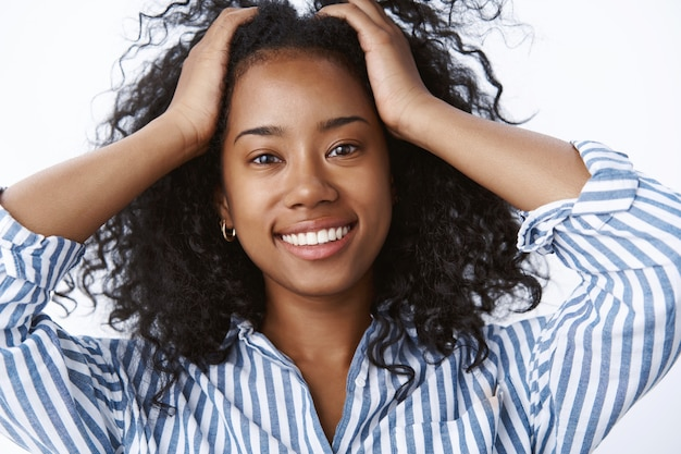 Close-up carefree relaxed tender african-american positive girl playing curls put hands through haircut smiling broadly feeling relaxtion freedom happiness, enjoying sunbeams warm spring weekend