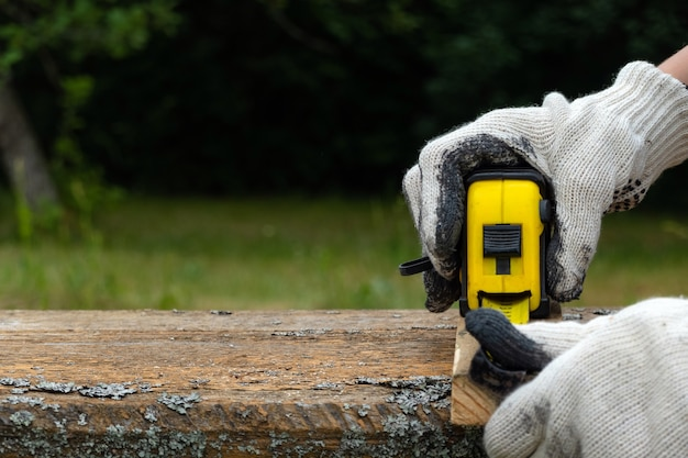 Close up of carpenter hand wearing working gloves and measuring plank with a tape measure.