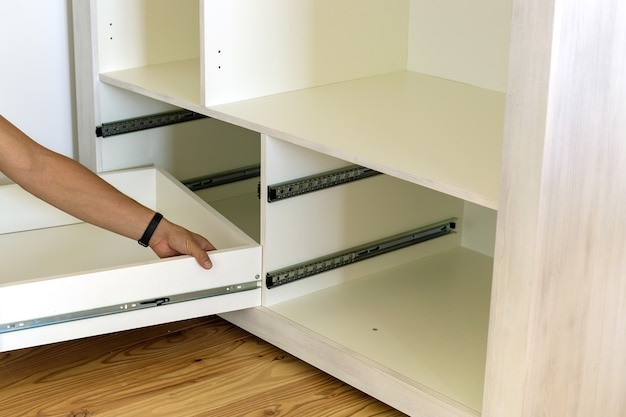 Close up of carpenter hands installing wooden drawer on sliding skids in contemporary cupboard cabinet.