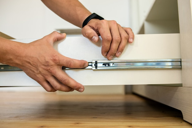 Close up of carpenter hands installing wooden drawer