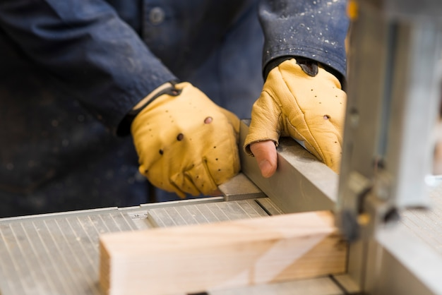 Close-up of a carpenter hands working with wooden block on workbench