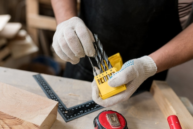 Close up of carpenter man holding  set of metal drills of various sizes for electric drill