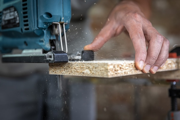 Close-up of a carpenter's hands in the process of cutting wood with a jigsaw.