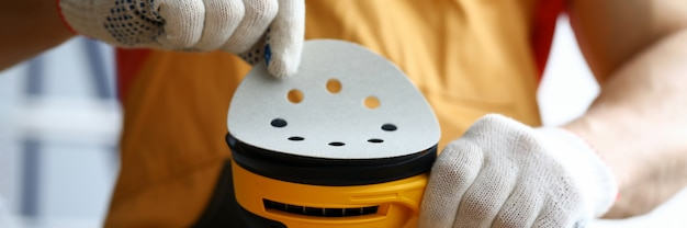 Close-up of carpenter worker changing disc on yellow sander machine. construction repairman in white protective gloves. equipment for polishing wood. renovation and handyman concept